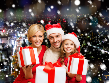 christmas, holidays,  family and people concept - happy mother, father and little girl in santa helper hats with gift boxes over snowy night city background photo