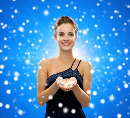 people, christmas, winter holidays and glamour concept - smiling woman in evening dress with diamond over blue snowy background photo