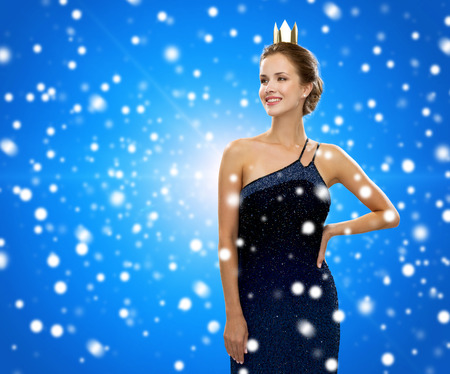 people, holidays, royalty and christmas concept - smiling woman in evening dress wearing golden crown over blue snowy background photo