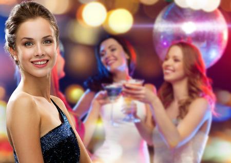 svátky, strana a lidé koncepce - usmívající se žena ve večerních šatech nad disco pozadí