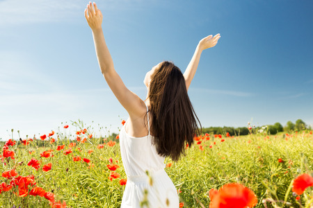 happiness, nature, summer, vacation and people concept - young woman dancing on poppy field from back photo