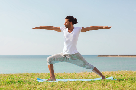 fitness, sport, people and lifestyle concept - smiling man making yoga exercises on mat outdoors photo