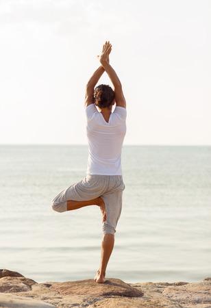 hombre flaco: fitness, deporte, la gente y el estilo de vida concepto - joven haciendo ejercicios de yoga en la playa de la parte posterior