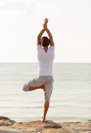 yoga man: fitness, sport, people and lifestyle concept - young man making yoga exercises on beach from back Stock Photo