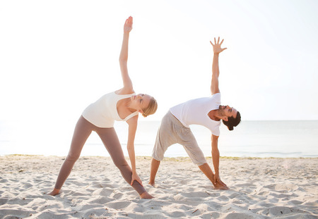 fitness, sport, friendship and lifestyle concept - couple making yoga exercises on beach