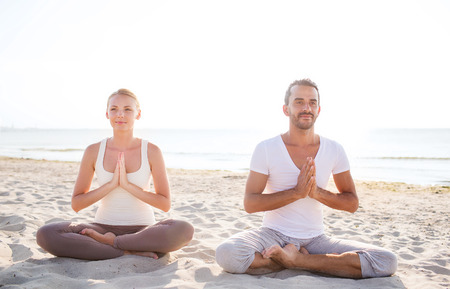 yoga beach: fitness, sport, friendship and lifestyle concept - smiling couple making yoga exercises sitting on sand outdoors