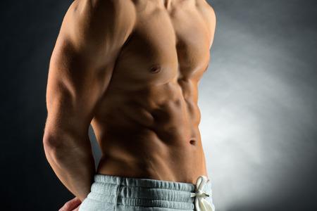 partes del cuerpo humano: deporte, el culturismo, la fuerza y ??la gente concepto - cerca del hombre joven de pie sobre fondo negro