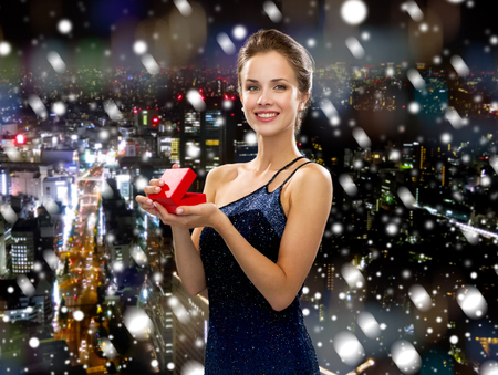 christmas, holidays and people concept - smiling woman in evening dress with small red gift box over snowy night city background photo