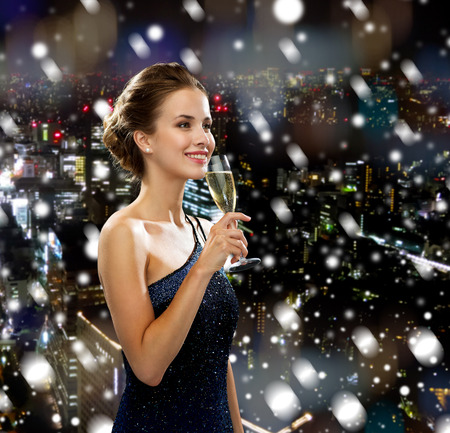 drinks, holidays, christmas, people and celebration concept - smiling woman in evening dress with glass of sparkling wine over snowy city background photo