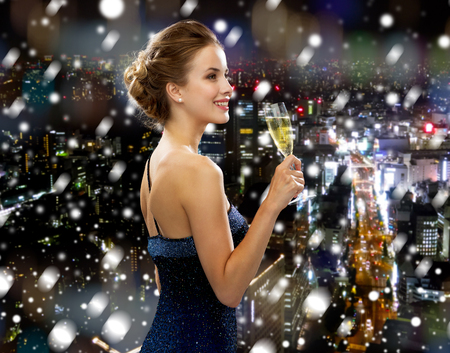 drinks, christmas, holidays and people concept - smiling woman in evening dress with glass of sparkling wine over snowy night city background photo
