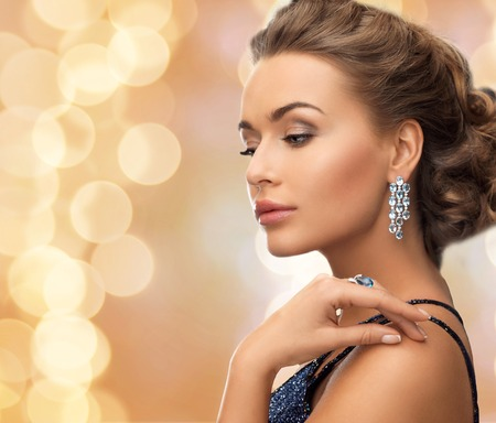people, holidays and glamour concept - beautiful woman in evening dress wearing ring and earrings over beige lights background Stockfoto