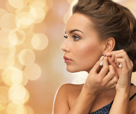earring: people, holidays, christmas and glamour concept - close up of beautiful woman wearing earrings over beige lights background