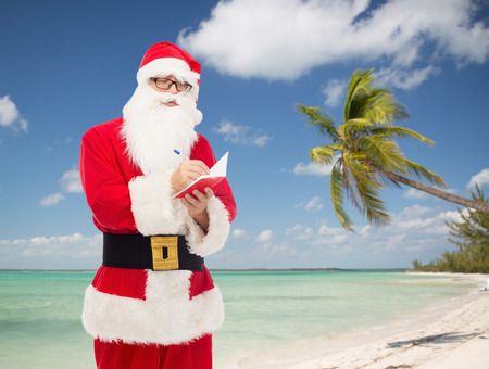 christmas, holidays, travel and people concept - man in costume of santa claus with notepad and pen over tropical beach background photo