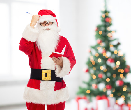 christmas, holidays and people concept - man in costume of santa claus with notepad and pen over living room with tree background photo
