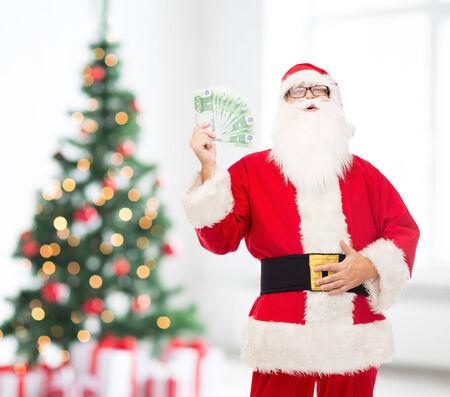 dinero euros: navidad, días de fiesta, ganando, la moneda y la gente concepto - el hombre en el traje de Papá Noel con el dinero del euro en la sala de estar con el árbol