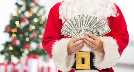 Kerstmis, vakantie, het winnen, munt en mensenconcept - sluit omhoog van de Kerstman met dollargeld over woonkamer met boom