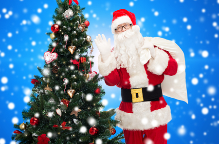 christmas, holidays and people concept - man in costume of santa claus with bag and christmas tree waving hand over blue snowy background photo
