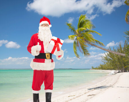 christmas, holidays, travel and people concept - man in costume of santa claus with gift box showing thumbs up gesture over tropical beach background photo