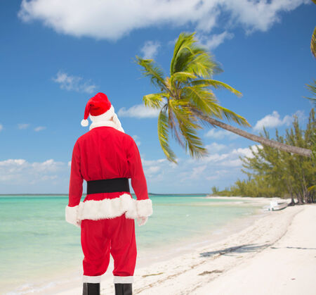 christmas, holidays and people concept - man in costume of santa claus from back over tropical beach background photo