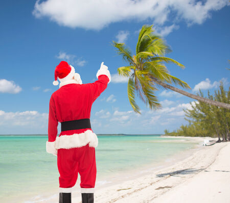 christmas, holidays and people concept - man in costume of santa claus pointing finger from back over tropical beach background photo