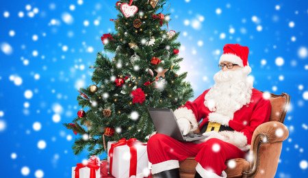 technology, holidays and people concept - man in costume of santa claus with laptop computer, gifts and christmas tree sitting in armchair over blue snowy background photo