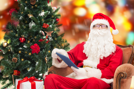 technology, holidays and people concept - man in costume of santa claus with tablet pc computer, gifts and christmas tree sitting in armchair over red lights background photo