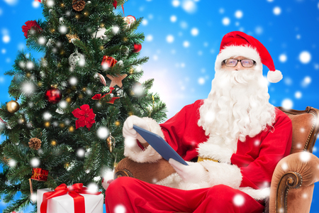 technology, holidays and people concept - man in costume of santa claus with tablet pc computer, gifts and christmas tree sitting in armchair over blue snowy background photo