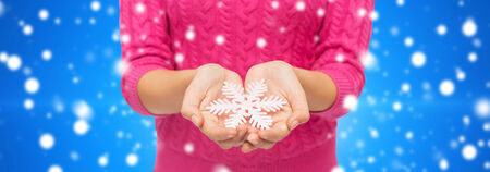 christmas, holidays and people concept - close up of woman in pink sweater holding snowflake blue snowy background photo