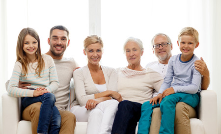 rodina, štěstí, generace a lidé koncept - šťastná rodina sedí na gauči doma