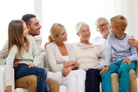 familie, geluk, generatie en mensen concept - happy family zitten op de bank thuis