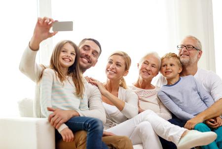 la familia, la felicidad, la generación y la gente concepto - la familia feliz sentado en el sofá y hacer Autofoto con el teléfono inteligente en el hogar