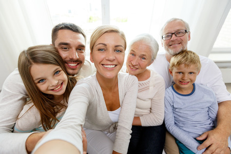 three generation: family, happiness, generation and people concept - happy family sitting on couch and making self portrait with camera or smartphone at home
