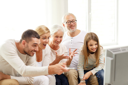family, happiness, generation and people concept - happy family sitting on sofa and watching tv at home photo