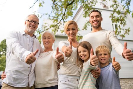 family, happiness, generation, home and people concept - happy family standing in front of house and showing thumbs up outdoors Stock Photo