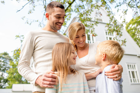 lifestyle woman: family, happiness, generation, home and people concept - happy family standing in front of house outdoors Stock Photo