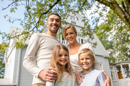 family, happiness, generation, home and people concept - happy family standing in front of house outdoors Stockfoto