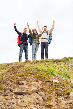 geologists: travel, tourism, hike, gesture and people concept - group of smiling friends with backpacks raising hands outdoors