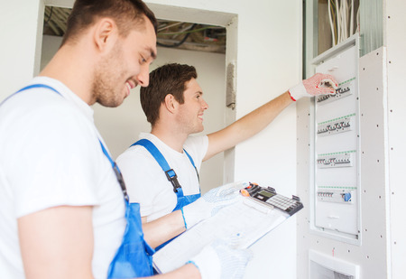 business, building, teamwork and people concept - group of smiling builders with clipboard and electrical panel indoors Stockfoto