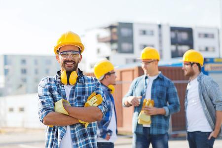 trabajadores: negocio, construcción, trabajo en equipo y concepto de la gente - grupo de sonrientes constructores de cascos al aire libre Foto de archivo