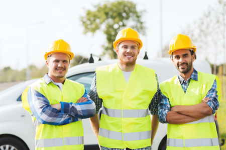 co workers: business, building, teamwork and people concept - group of smiling builders in hardhats on car background outdoors