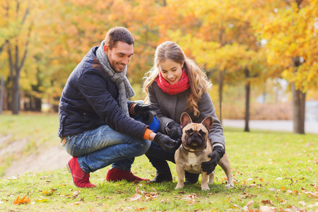 care, animals, family, season and people concept - smiling couple with dog in autumn park photo