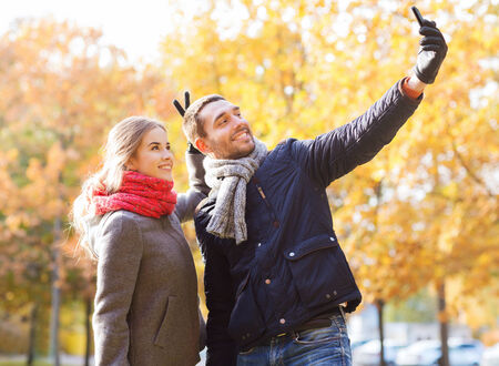love, relationship, family and people concept - smiling couple hugging and taking selfie with smartphone in autumn park photo