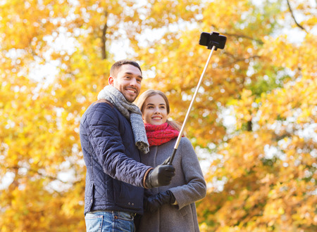 love, relationship, family and people concept - smiling couple hugging and taking selfie with smartphone and monopod in autumn park