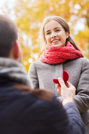 love, family, autumn and people concept - close up of smiling couple with engagement ring in small red gift box outdoors photo