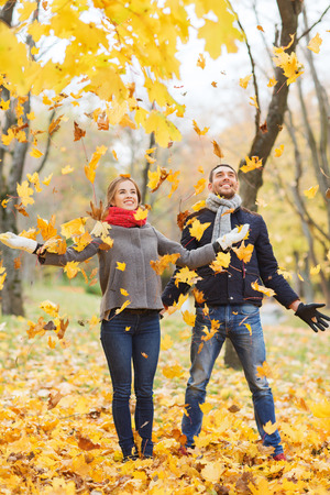 love, relationship, family, season and people concept - smiling couple throwing leaves and having fun in autumn park