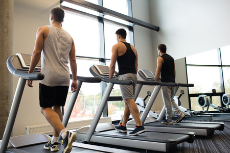 treadmill: sport, fitness, lifestyle, technology and people concept - men exercising on treadmill in gym Stock Photo