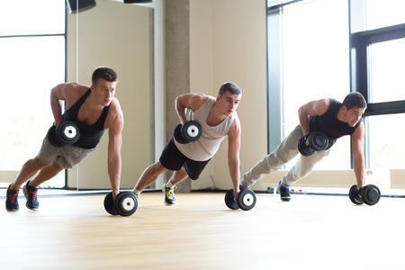 push: sport, fitness, lifestyle and people concept - group of men with dumbbells in gym Stock Photo