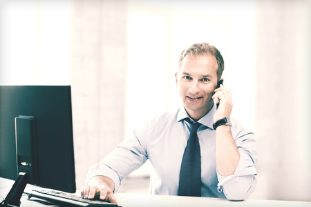 business and technology concept - smiling businessman with smartphone in office photo