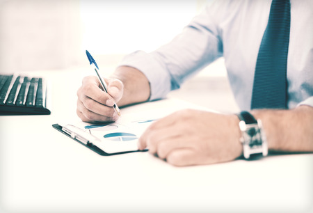business, office, school and education concept - businessman working and signing papers photo