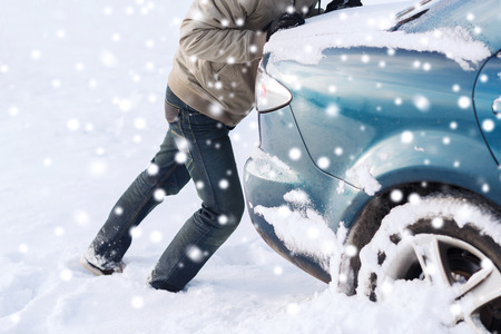 stuck: transportation, winter, people and vehicle concept - closeup of man pushing car stuck in snow Stock Photo